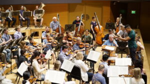 Conductor with orchestra at practice session